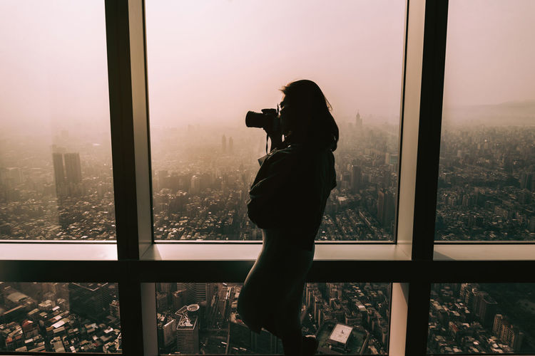 Side view woman photographing through window against cityscape
