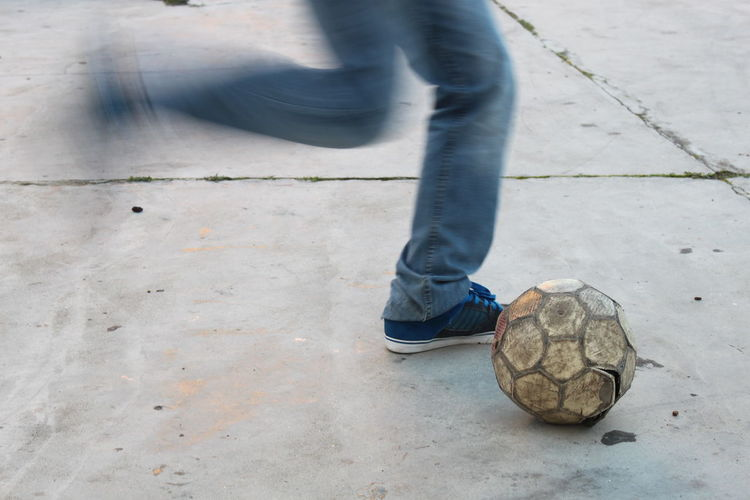 Low section of man kicking football on street