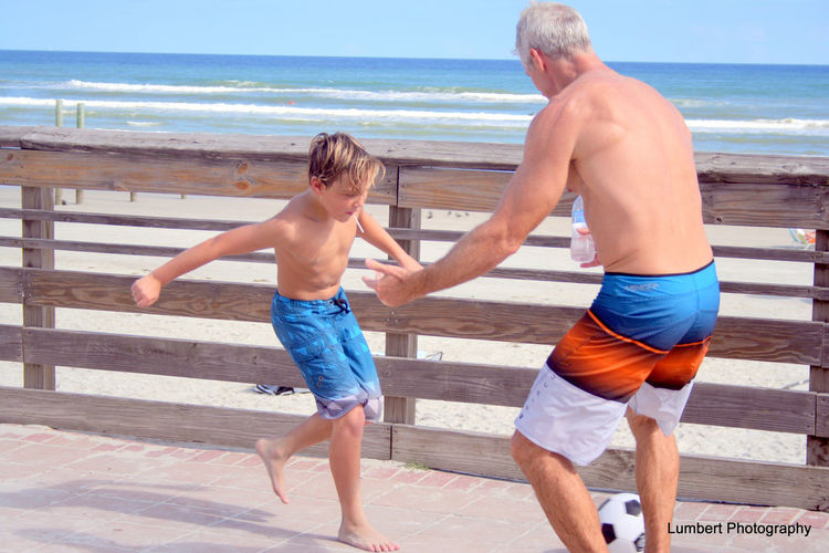 Young Boy And Man With Soccer Ball Playing Keep Away fun on Boardwalk