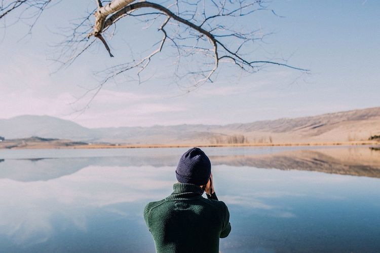 Real People One Person Tree Water Reflection Lifestyles Rear View Nature Lake Leisure Activity Sky Day Bare Tree Scenics Outdoors Beauty In Nature