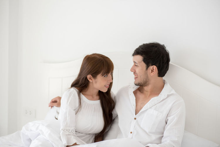 Adult Bonding Boyfriend Couple - Relationship Front View Girlfriend Heterosexual Couple Indoors  Lifestyles Love Men Positive Emotion Sitting Smiling Togetherness Two People Waist Up Women Young Adult Young Couple Young Men Young Women