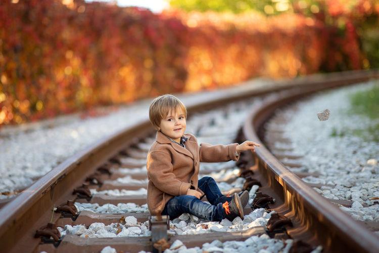 Full length of boy sitting on railroad track