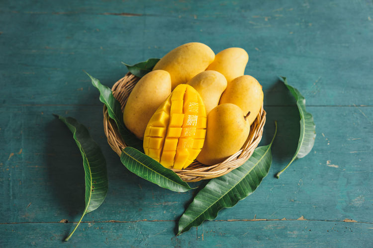 Mango in the basket Food Food And Drink Freshness Healthy Eating Wellbeing Fruit Table Still Life Leaf Indoors  Plant Part Wood - Material Basket Yellow Citrus Fruit No People Orange Color Directly Above High Angle View Green Color Orange
