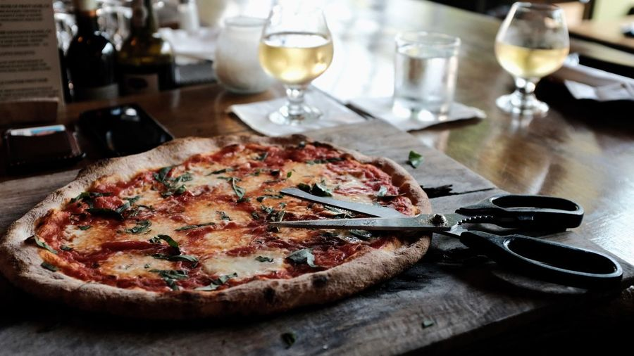 Close-up of pizza and scissor on table