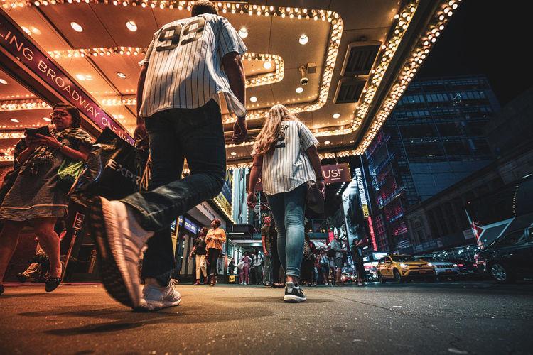 Group of people walking on illuminated street at night