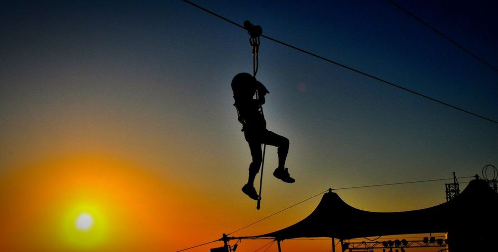 Low Angle View Of Silhouette Man Zip Lining Against Clear Sky During Sunset