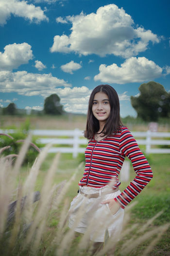 Portrait of smiling young woman standing on field against sky