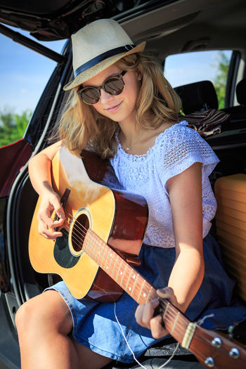 Girl playing guitar while sitting in car