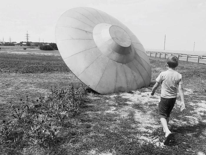 Rear View Of Boy Walking On Field Towards Artificial Ufo