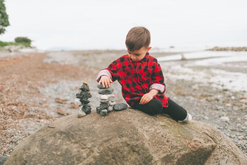 Rear view of boy sitting on rock