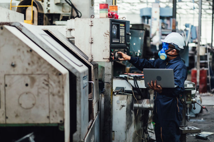 Side view of man using laptop in factory