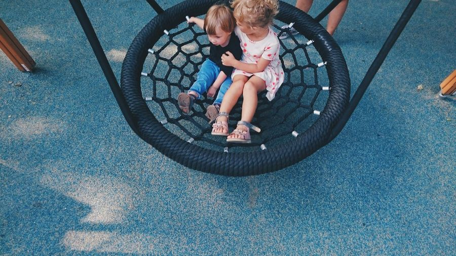 High angle view of siblings sitting on swing at playground