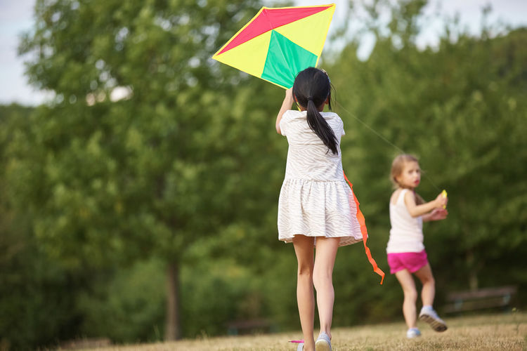 Female friends with kite at park
