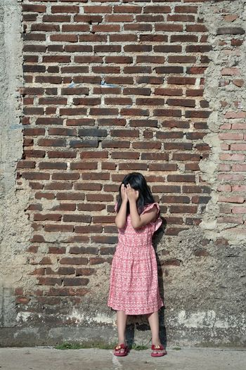 Being grounded pose series, ISO 100 1/640 s f/5.6 45 mm Bandung Shooter Indonesian Shooter One Person Brick Wall Real People Brick Wall Women Child Full Length Standing Females Wall - Building Feature Girls Lifestyles Childhood Architecture Built Structure Day Dress Emotion Innocence Depression - Sadness Hairstyle