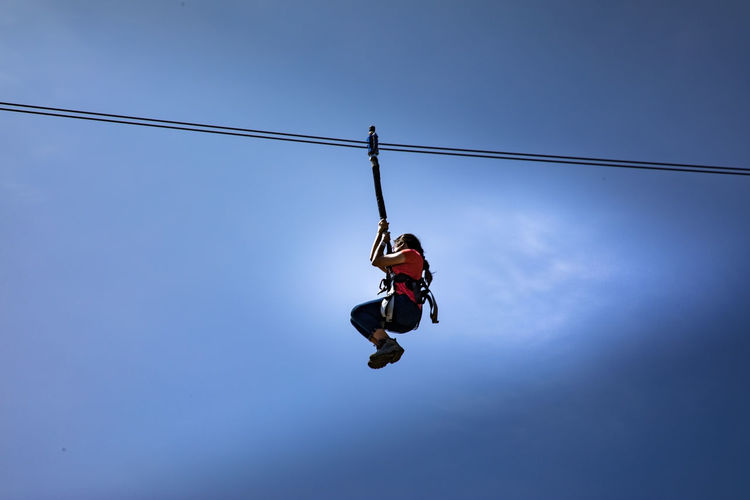 Low Angle View Of Woman Zip Lining Against Sky