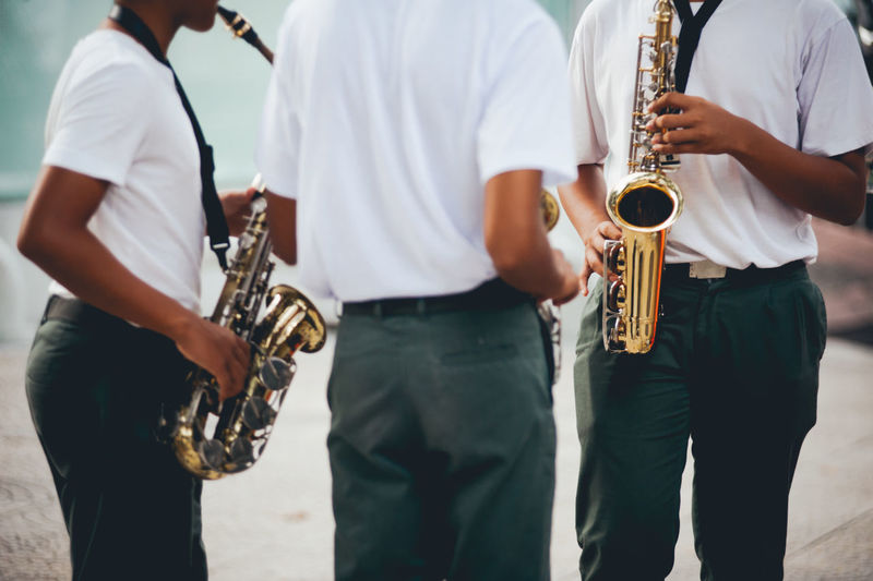 Midsection of men playing saxophones