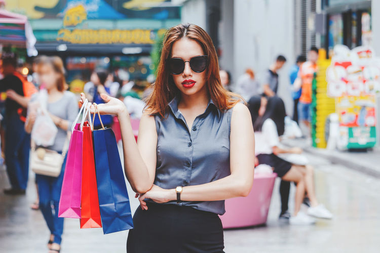 Portrait Of Young Woman With Shopping Bags Outside In Mall