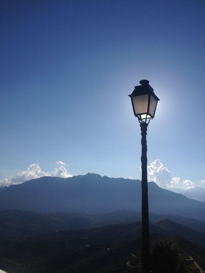 Gas light by mountains against sky