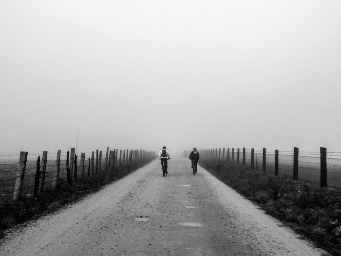 Cycling Black & White Winter Adult Adults Only Blackandwhite Clear Sky Copy Space Cyclingphoto Day Full Length Men Monochrome Monochrome _ Collection Monochrome Photography Monochrome_life Nature Outdoors People Real People Rear View Shootermag Sky Two People Walking Women