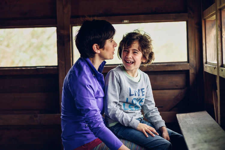Smiling mother and daughter sitting in log cabin