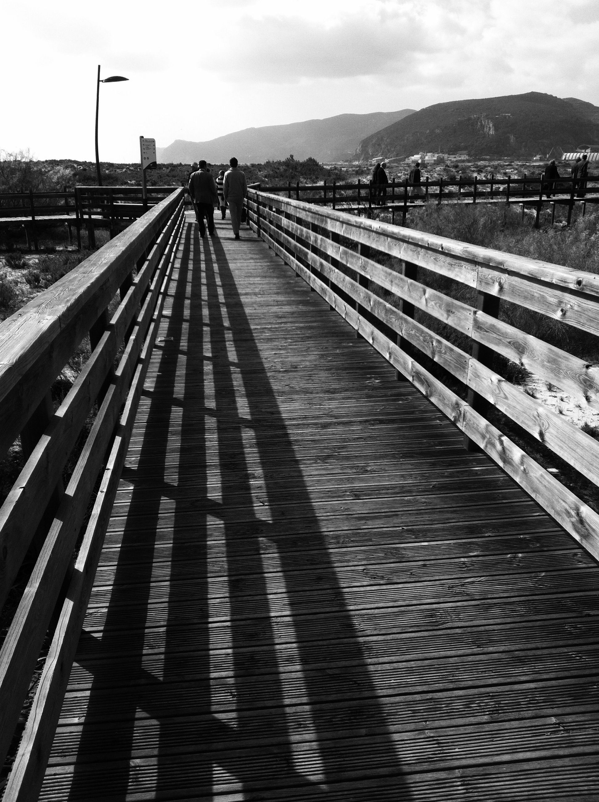 the way forward, sky, walking, diminishing perspective, lifestyles, railing, vanishing point, men, leisure activity, built structure, rear view, architecture, full length, unrecognizable person, incidental people, cloud - sky, sunlight