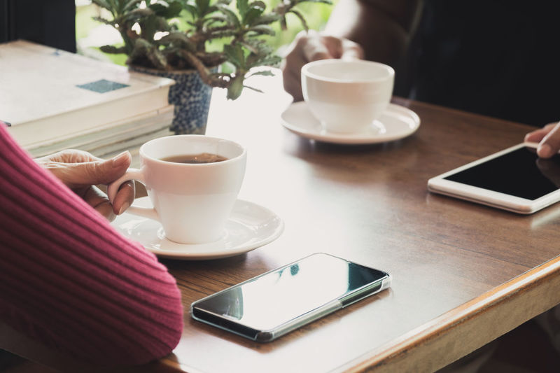 Female's hand holding a tea cup on wooden table. Table Cup Mug Drink Food And Drink Coffee Refreshment Coffee - Drink Coffee Cup Human Hand One Person Crockery Indoors  Wireless Technology Mobile Phone Technology Communication Portable Information Device Saucer Smart Phone Hand Hot Drink Tea Cup