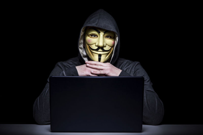 Man in mask with laptop against black background