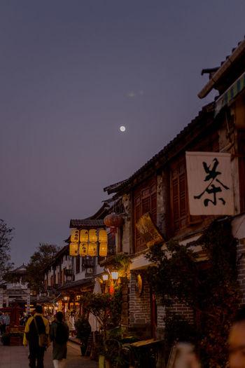 People on street against illuminated buildings at night