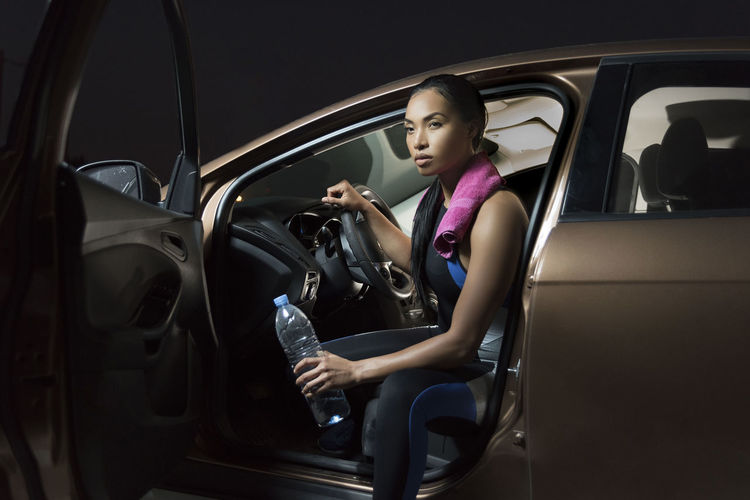Beautiful woman holding bottle while sitting in car at night