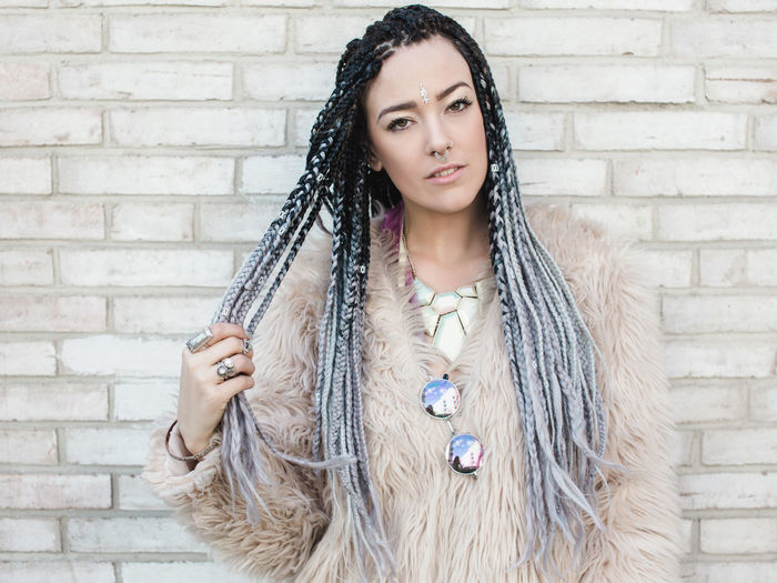 Portrait of a fashion forward young woman in front of the brick wall Braids Cool Coolin Fashion Hair Stunning Adult Beautiful Woman Beauty Brick Brick Wall Fashionista Hair Hairstyle Lifestyles Long Hair Looking At Camera One Person Portrait Real People Wall Warm Clothing Women Young Adult Young Women