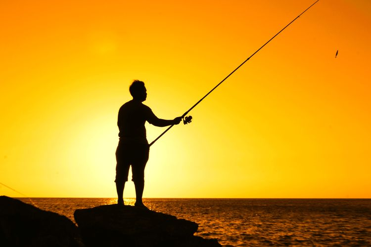 Man standing on rock while fishing in sea against orange sky