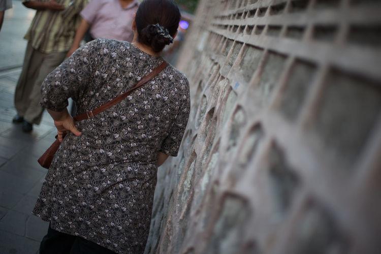 Rear View Of Woman On Sidewalk