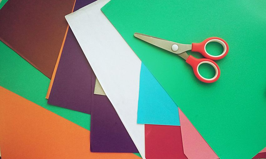 High angle view of multi colored papers and scissors on table