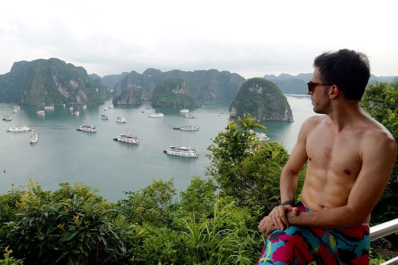 Shirtless Man Looking At Ha Long Bay While Sitting On Railing
