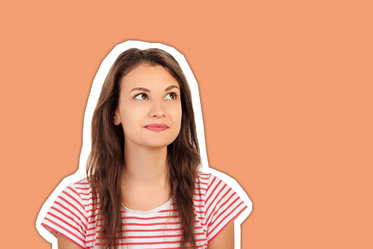 Portrait of a beautiful young woman against orange background