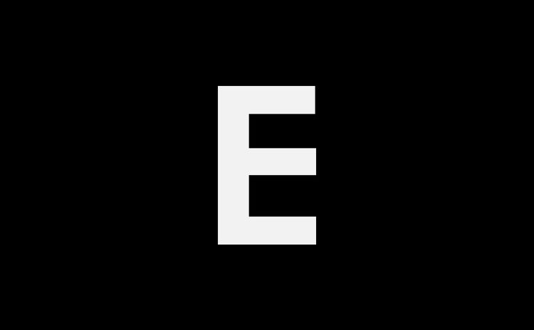Tall ship sailing on sea against orange sky