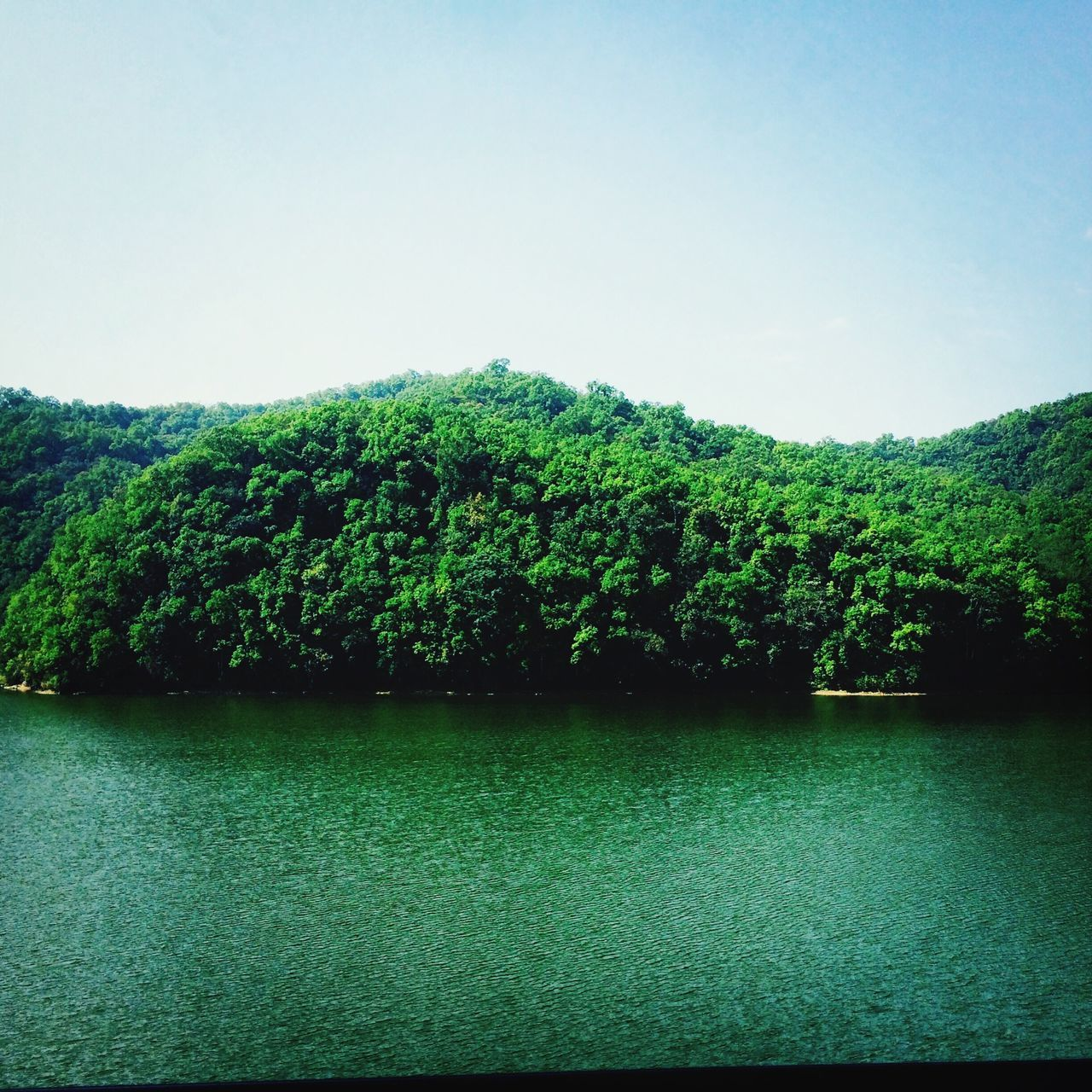Scenic View Of Calm Lake Against Blue Sky