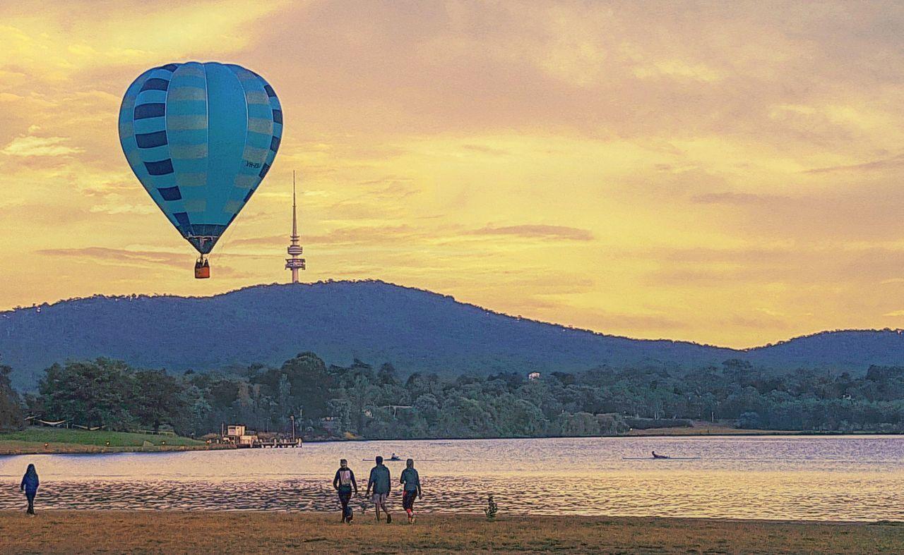 HOT AIR BALLOON FLYING OVER BEACH AGAINST SKY