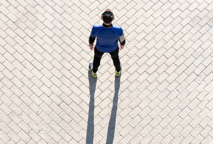 High angle view of man standing on footpath