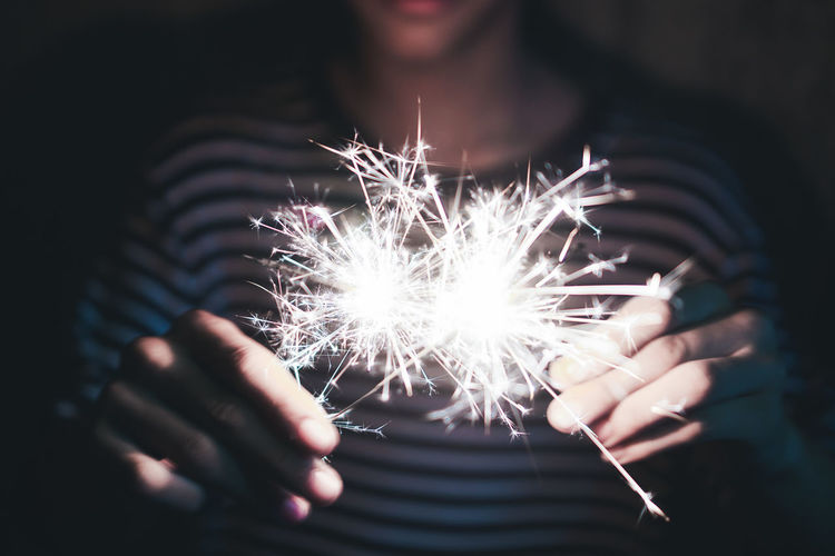Midsection of person holding illuminated sparklers