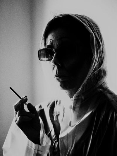 Close-up of woman wearing sunglasses holding cigarette