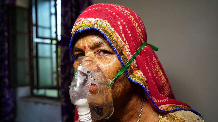 Close-up portrait of woman wearing oxygen mask at home