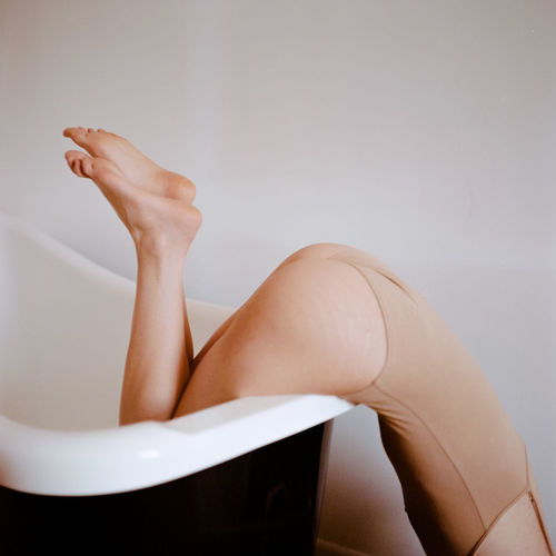 Low section of woman bending over bathtub at home