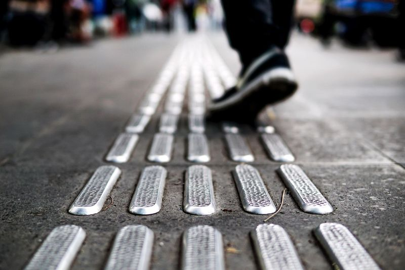 Low section of man walking on tactile paving in city