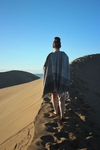 Rear view of man standing on desert against clear sky