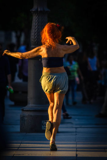 Rear View Of Woman Dancing On Footpath