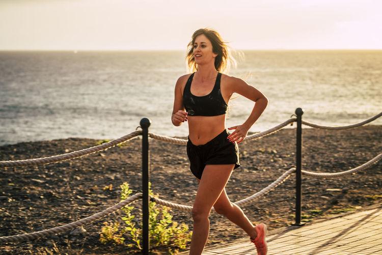 Smiling woman jogging against sea