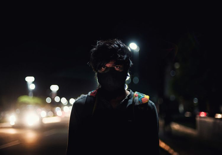 Portrait of young man standing on road at night