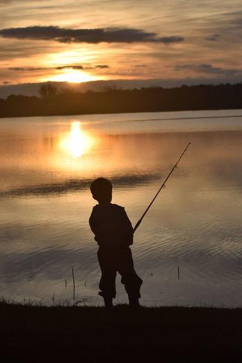 Silhouette man fishing on shore against sunset sky