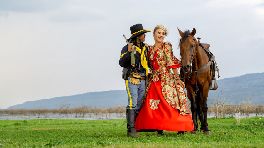 Man and woman in traditional clothing standing by horse on field against sky